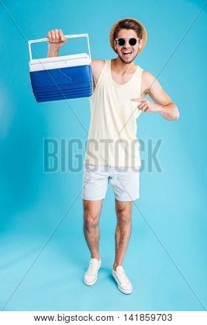 Happy young man in hat and sunglasses holding and pointing on cooler bag over blue background