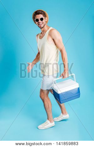 Smiling young man in hat and sunglasses walking and holding cooler bag over blue background