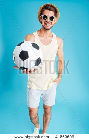 Cheerful young man in hat and sunglasses giving you a football ball over blue background