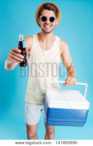 Cheerful young man in hat and sunglasses giving you cooling bag and bottle of soda over blue background