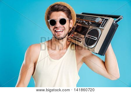 Portrait of happy young man in hat and sunglasses with boombox over blue background