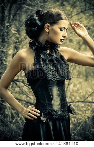 Magnificent brunette woman in black old-fashioned dress walking in the thicket of the forest. Gothic style. Fashion.
