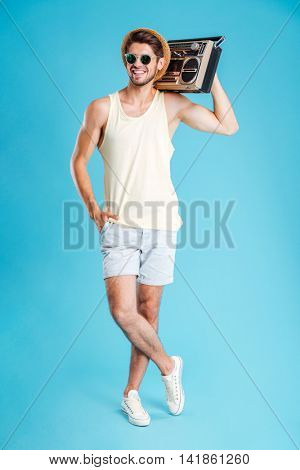 Full length of smiling young man in shorts, hat and sunglasses holding boombox over blue background