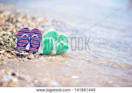 Kids flip flops on beach in front of the blue sea