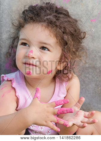 Baby girl is playing with paints outdoors