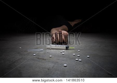 Close-up on the floor of the syringe with the drug. In the background a young drug addict