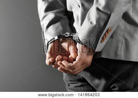 Man in handcuffs on grey background