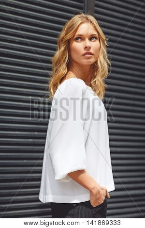 Outdors portrait of young beautiful blonde woman looks up and holds hand in pockets