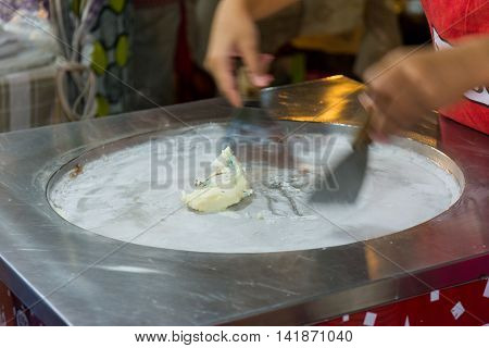 Thai woman cooking fresh handmade ice rolls in night market. Koh Samui Thailand