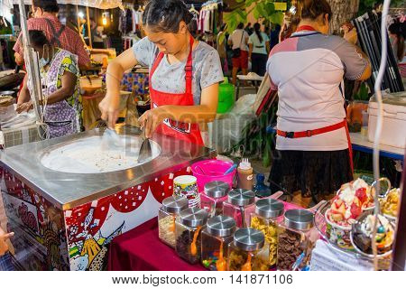 Koh Samui Thailand - July 4 2016. Thai woman cooking fresh handmade ice rolls in night market. Koh Samui Thailand