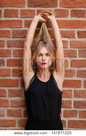 Young cute blond girl holding her hair up on outstretched hands, stylish image
