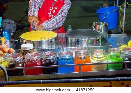 Koh Samui Thailand - July 04 2016. Thai man cooking fresh pancake in Koh Samui Thailand
