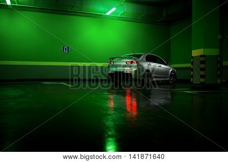 Moscow, Russia - June 18, 2016: Gray car Mitsubishi Lancer stay at underground parking lot and reflect in wet asphalt