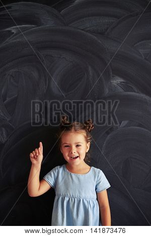 A pleased pretty girl exclaimed almost with inspiration while posing against a blackboard