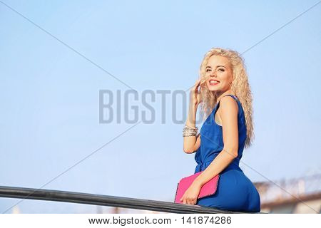 Fashionable young woman sitting on railing