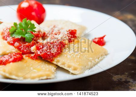Homemade ravioli with tomato sauce parsley and parmesan cheese on a white plate closeup