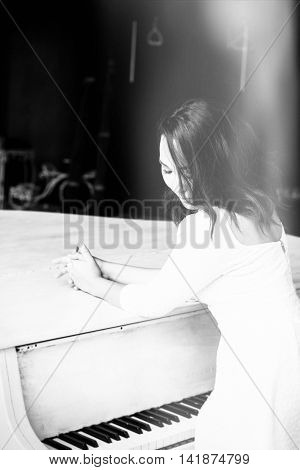 beautiful brunette girl standing at a piano. monochrome shoot.