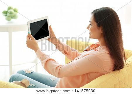 Pregnant woman with tablet in room