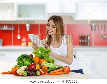 Woman with tablet and healthy food in the kitchen