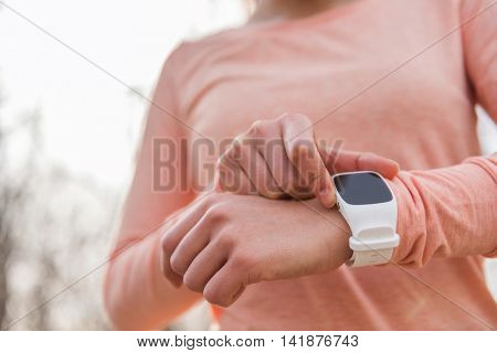 Active woman getting ready setting smartwatch as fitness monitor. smart watch running athlete preparing for cardio workout run race. Sportswoman checking device in cold weather autumn, spring or fall.