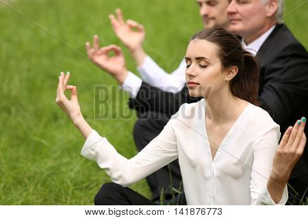 Business people relaxing in meditation pose in park