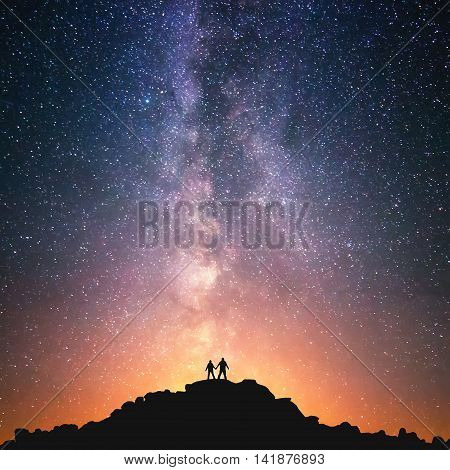 Silhouttes of two people standing together holding hands against the Milky Way on the top of the hill.