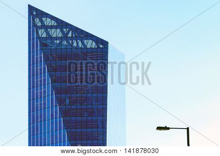Modern office building and a lamppost against a blue cloudless sky