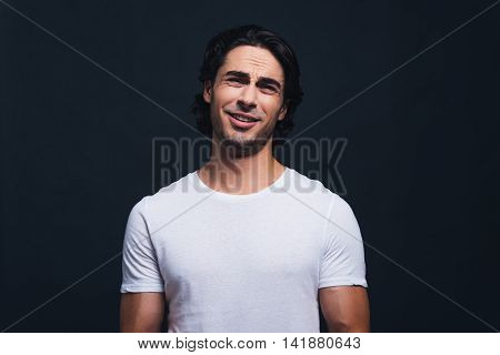 You think so? Portrait of young man expressing irony and looking at camera while standing against grey background