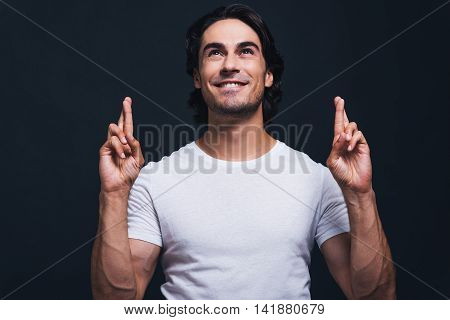 Waiting for special moment. Handsome young smiling man keeping fingers crossed and looking up with smile while standing against grey background
