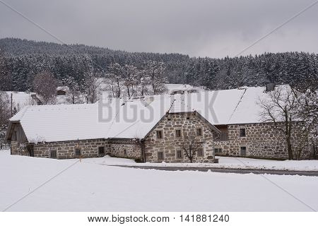 old farmhouses with idyllic stone walls in snowy winter landscapes
