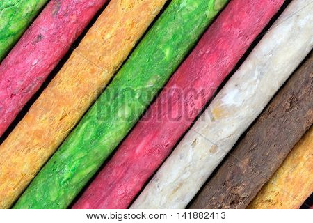 A very close view of dyed beef hide dog treats on a black background.