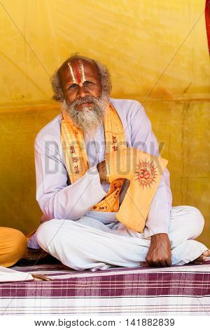 ALLAHABAD, INDIA -  FEB 14th - A brahmin priest of the Vaishnava Ramanandi sect chanting on beads in a small bag at the Kumbha Mela on February 14th 2013