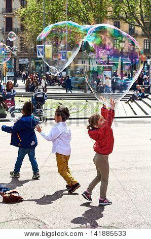 Barcelona Spain - April 3 2016: Children catching the soap bubbles in the Catalonia Square (Plaza de Cataluna) is a large square in central Barcelona