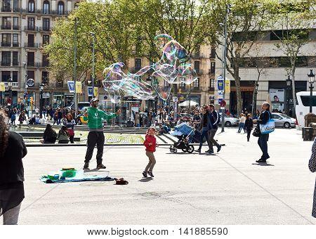 Barcelona Spain - April 3 2016: People enjoy the soap bubbles in the Catalonia Square (Plaza de Cataluna) is a large square in central Barcelona