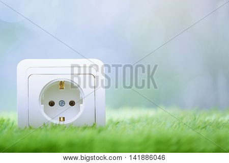 Electric outlet in the grass. Close-up photo