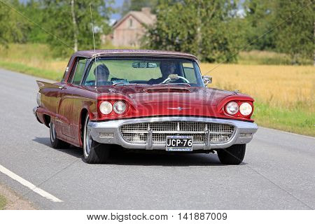 SOMERO, FINLAND - AUGUST 6, 2016: Red Ford Thunderbird hardtop 1960 classic car takes part in the 90 km Maisemaruise 2016 drive along scenic roads of Tawastia Proper Finland. Public event.