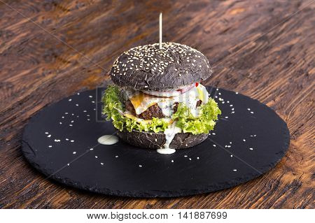 black burger with beef cutlet with vegetables sesame seeds on slate board on wooden background