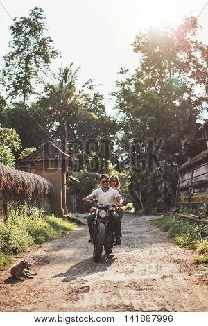 Couple Enjoying Motorcycle Ride Through A Village Road.