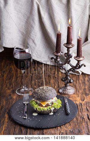 black burger with beef cutlet with vegetables sesame seeds on slate board on wooden background. in the background is brown chandelier with candles and a glass of wine.