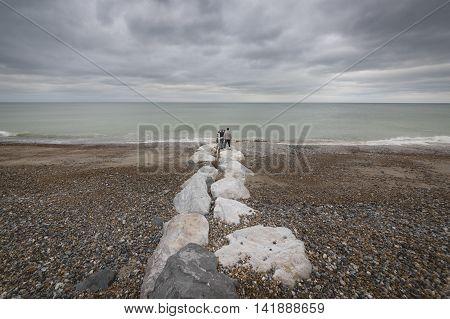 Couple walking at stony beach, uk coast