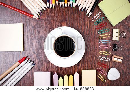 Top view of dark wooden desktop with variety of colorful stationery items around coffee cup. Close up