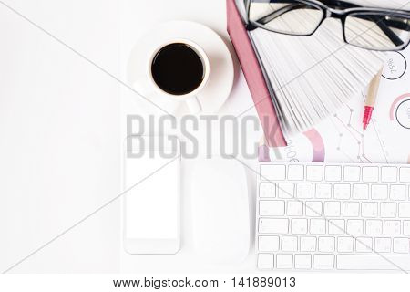 Top view of white office tabletop with blank cellular phone coffee cup computer mouse and keyboard glasses book pen and business report. Close up Mock up