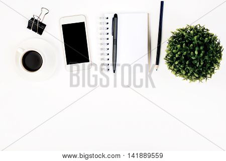 Top view of white office desktop with spiral notepad other stationery items blank smartphone coffee cup and plant. Mock up