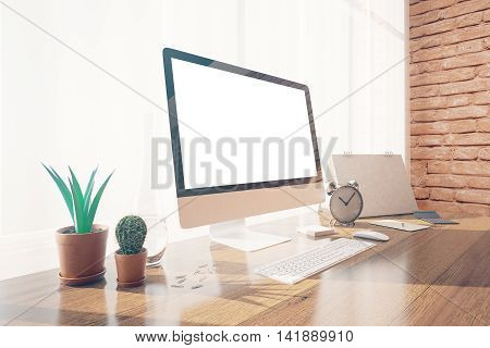 Side view of creative designer desktop with blank white pc monitor decorative plants keyboard and other items on brick wall background with daylight. Mock up 3D Rendering