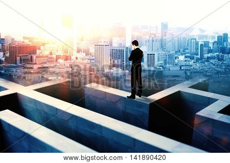 Businessman on top of concrete maze wall thinking on city background with sunlight