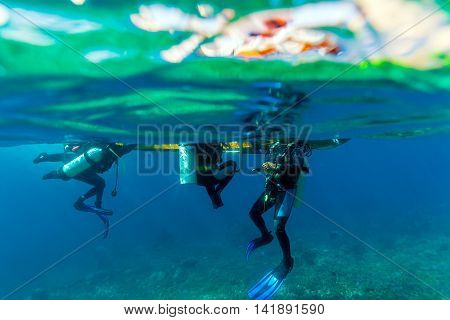Group of fout Divers Climbing into Boat