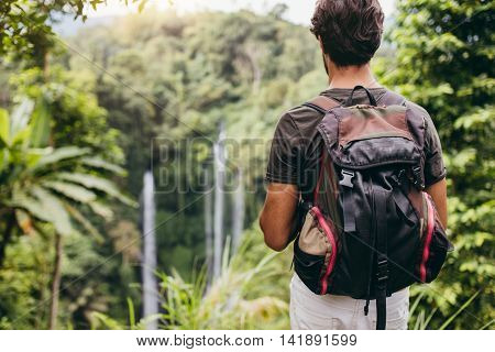 Rear view shot of male hiker with backpack standing on a cliff and looking at waterfall. Young man admiring the landscape in forest.