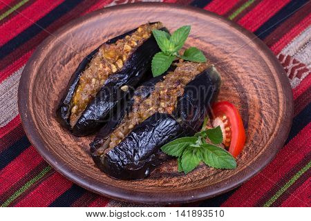 Baked eggplant stuffed with onions cherry plums and walnuts on the plate close up