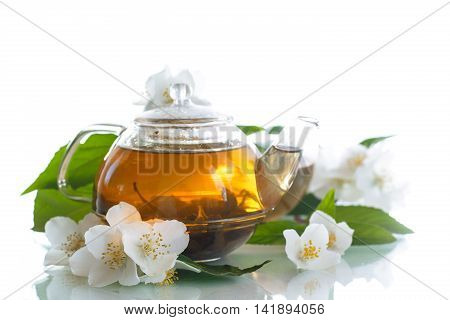 jasmine tea in a teapot with a branch of jasmine on white background