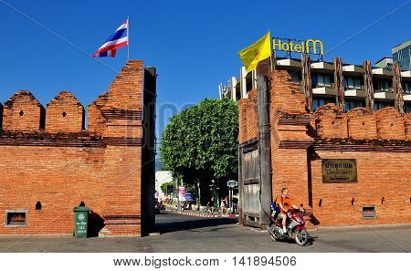 Chiang Mai Thailand - December 22 2012: A motorcylist driving past the Tha Phae Gate and ancient city defense walls with Hotel M in the background  *